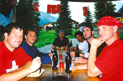 Nigel, Mason, John, Jeff, Adam, and Jim are enjoying food and Feldschlossen outside.